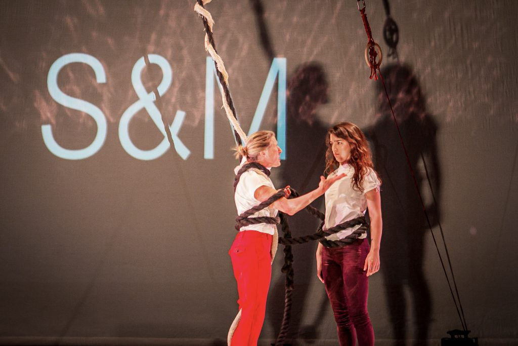Two femal actors on stage, with ropes wrapped round their bodies.