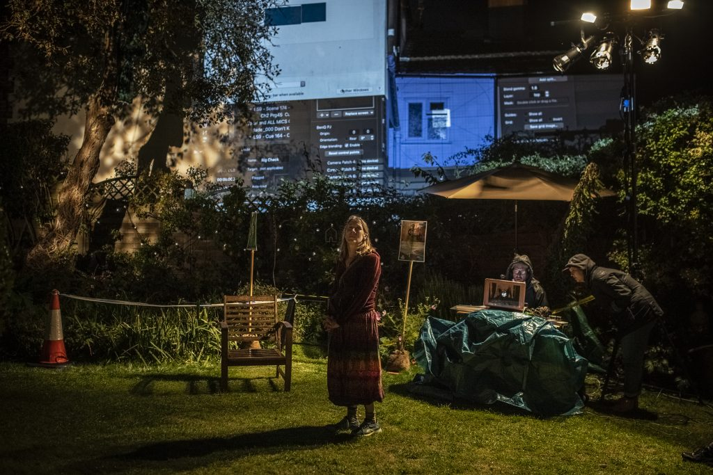 Photo of the author on the stage set in her garden, at night-time.