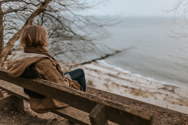 Woman sitting on a bench looking out onto the sea.