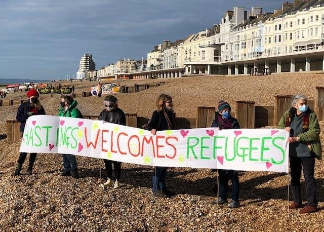 A group of people on the St Leonards / Hastings seafront, holding a banner reading 'Hastings welcomes refugees'
