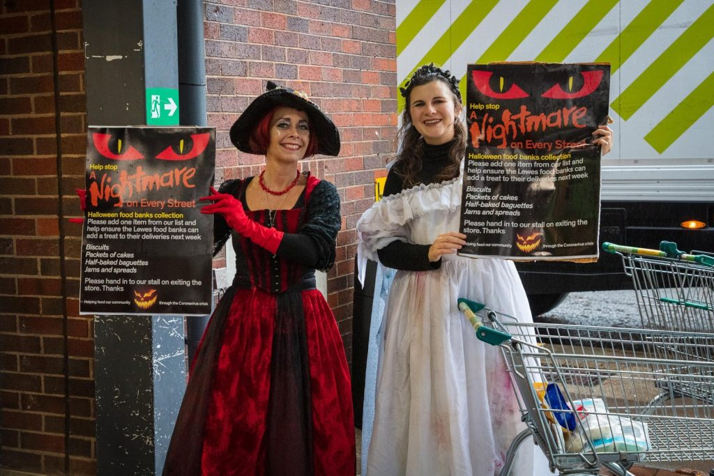 Volunteers Deirdre Daly and Daisy Jorgensen from Kaleidoscope Drama encourage shoppers to donate to the Halloween food bank collection. Photo credit: Nigel French