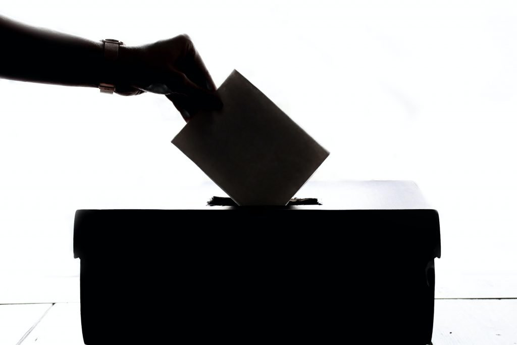 Close-up of a hand placing a voting paper into a ballot box.