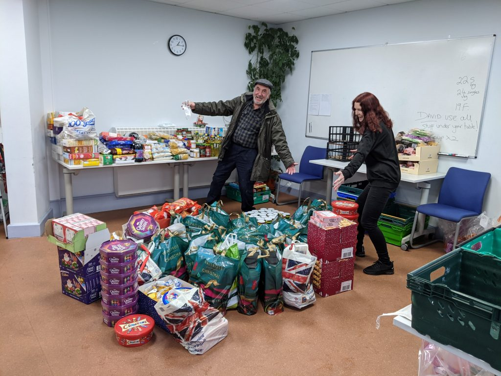 A man and a woman looking enthusiastically at boxes, bags and stacks of food items.