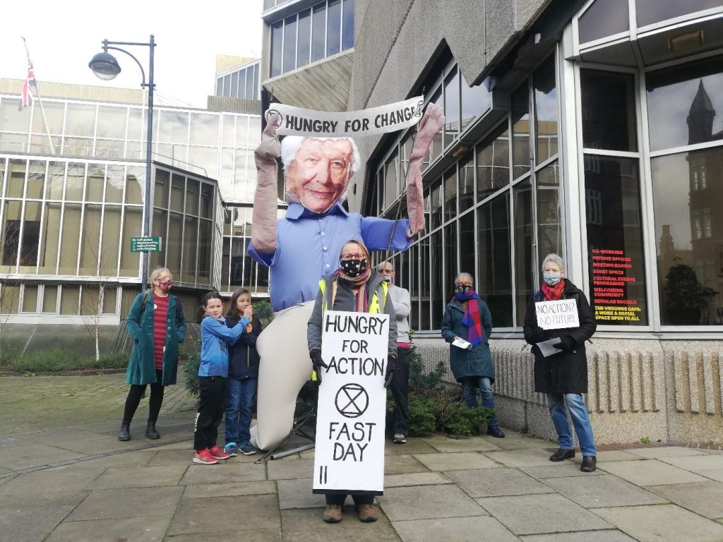 Photo of Venetia Carter holding her placard 'Hungry for Action Fast: Day 2'.  Behind her a group of campaigners and a large blow-up figure of David Attenborough.