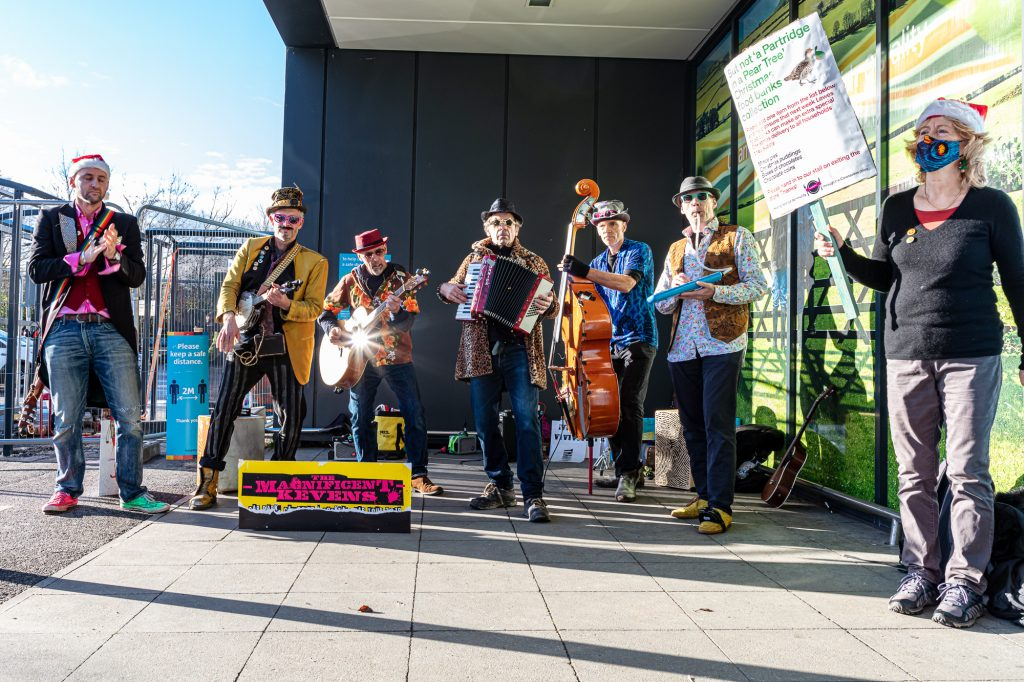 A group of musicians, dressed in colourful outfits, outside a supermarket.