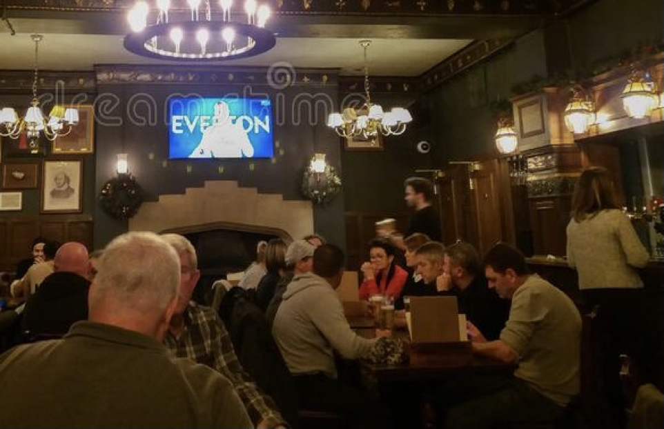 Interior pub scene, people at tables, overlooked by large TV screen