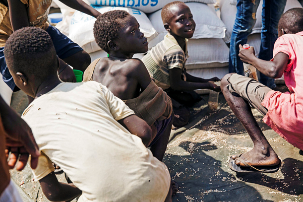 Undernourished young boys gather ing up leftover grain at a food distribution site.