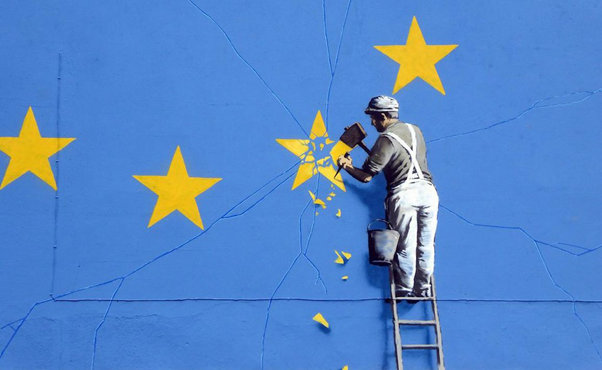 Yellow stars painted on a blue wall. A man with hammer and chisel is removing one of the stars.