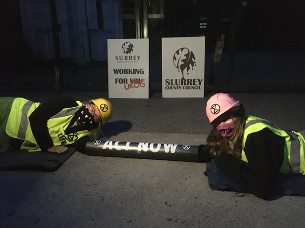 Photo of two Extinction Rebellion activists, wearing high-vis jackets and hard hats.