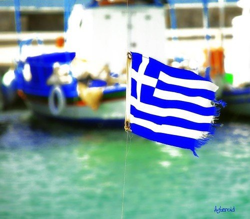 Greek flag, with a fishing boat in the background.