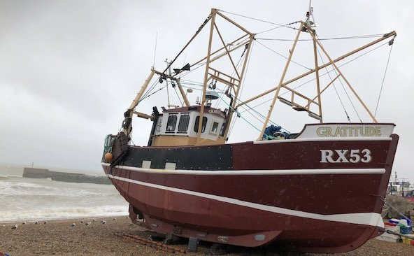 A fishing boat called Gratitude moored on the beach at Hastings.