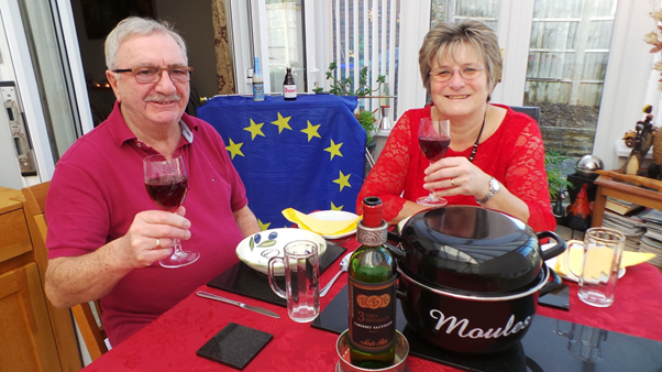 A couple sitting at a dinner table, raising glasses of red wine to toast their meal. A large pot labelled 'Moules' is on the table, an EU flag is draped over a cabinet in the background.