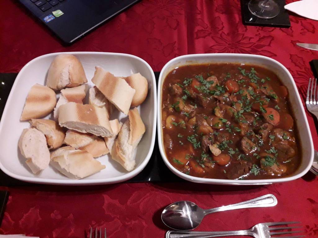 A bowl of stew and a bowl of sliced baguette.