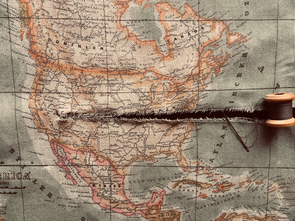A cloth map of the United States, with a large tear across the middle and a needle and thread indicating the tear ican be mended.
