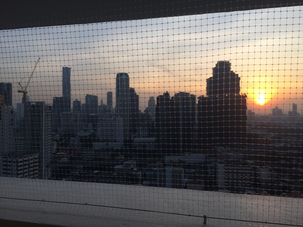 View from hotel balcony, screened by wire mesh, of sunset in Bangkok,