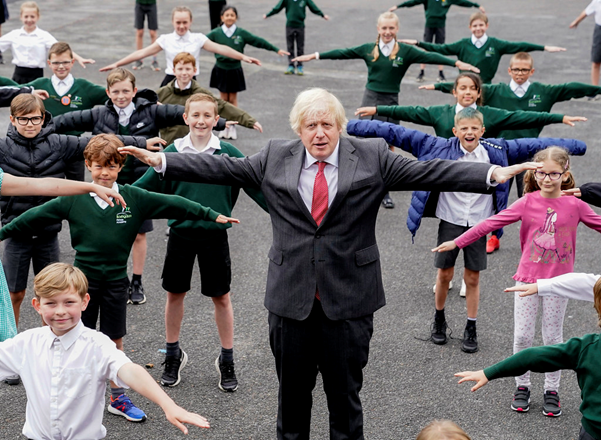 Boris Johnson and a group of children pictured in a school playground, all of them holding out both arms at shoulder height.
