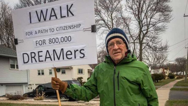 Alan Dornan carrying a placard that reads: I walk for a path to citizenship for 800,000 DREAMers.