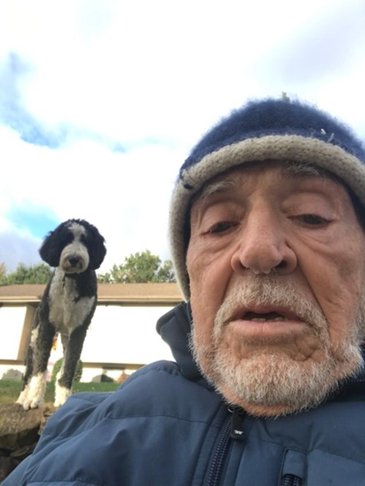 Alan Dornan taking a selfie, with dog Bentley in the background.
