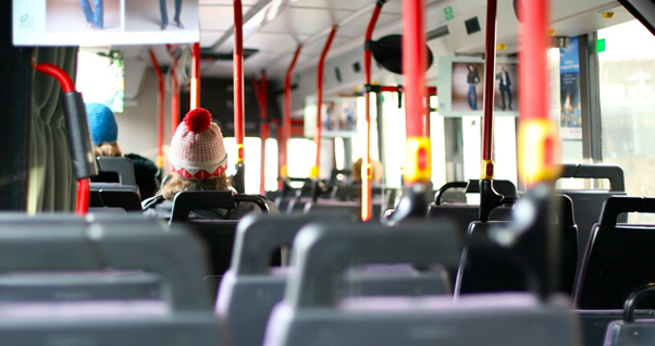 Photo of the inside of a bus, almost empty, looking forward from the rear.