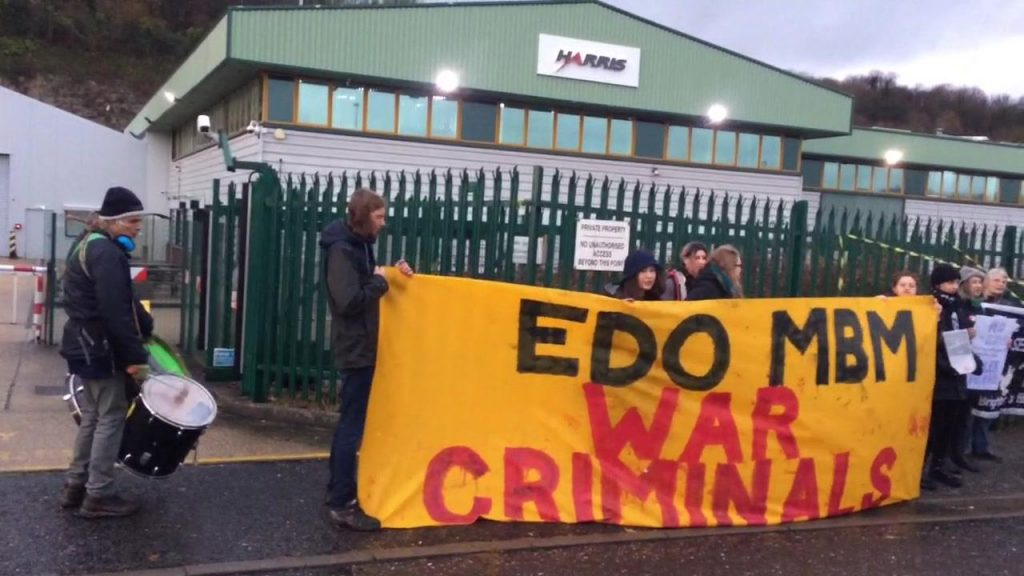 Protesters with a banner reading: EDO MBM War Criminals
