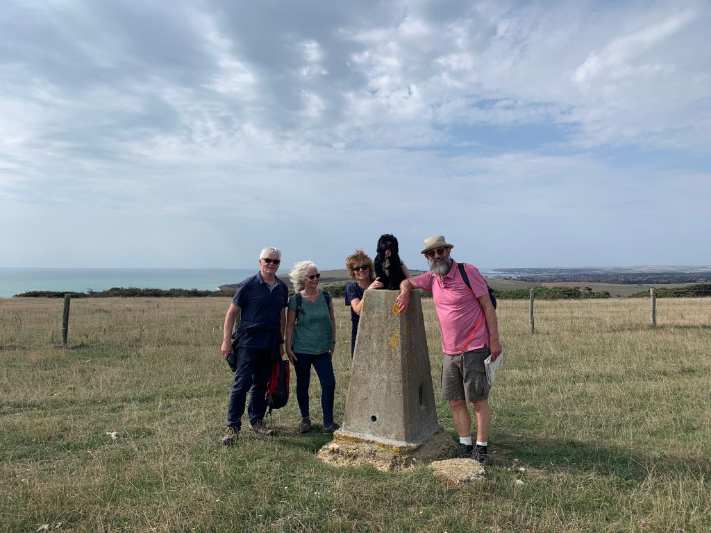 """James, Ringo and some """"bubble"""" walking companions pose for a photo at Haven Brow trig point near Seven Sisters, with the sea in the background"""