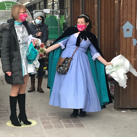 Woman dressed as Cinderella outside a supermarket, chatting to passersby.