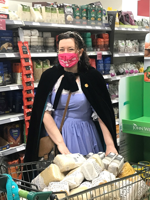 Woman dressed as Cinderella with a trolley loaded with pasta, rice and other staples.