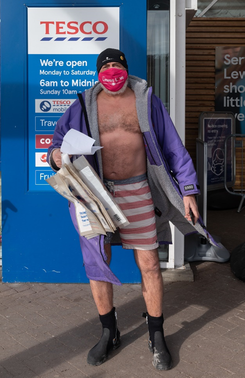 Man dressed in swimming trunks and a robe, ready to go shopping.
