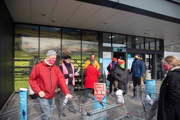 A group of people outside a supermarket.