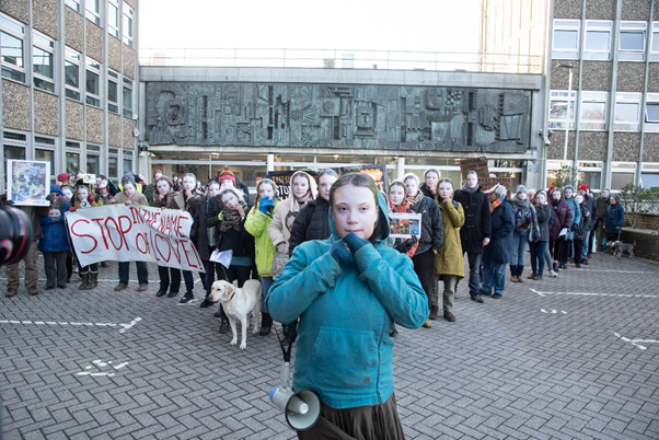 Group of protesters holding Great Thunberg masks in front of their faces.
