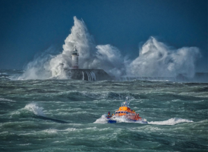 Lifeboat in stormy seas leaving Newhaven Harbour, with water crashing high above the harbour arm.