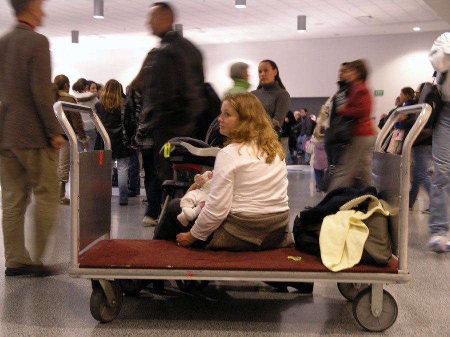 Mother with small baby, sitting on a luggage trolley at an airport.