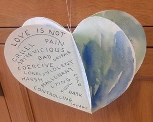 Paper heart hanging from a string, with words written on one side: Love is Not ... cruel, pain, vicious, bad, coercive, etc