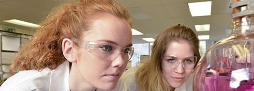 Two female science students at Sussex University in chemistry lab coats and goggles