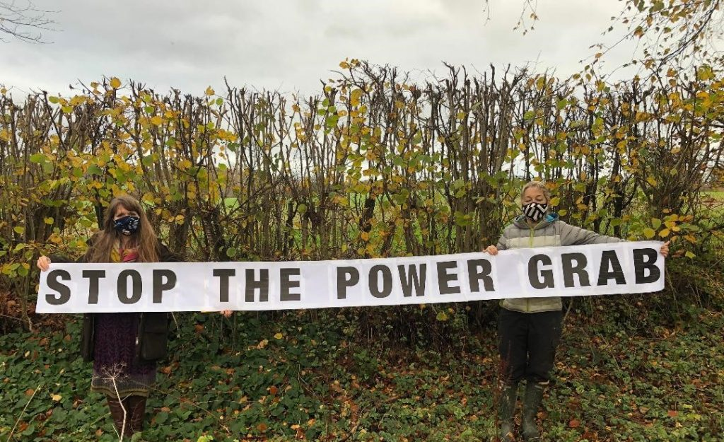 "Residents hold up a banner saying ""Stop the Power Grab"""
