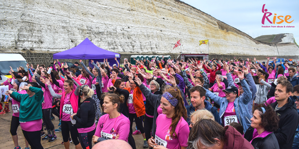 Runners (many wearing pink tops), at the start of a race on Brighton seafront.
