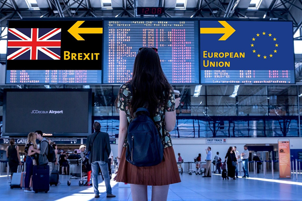 Young woman standing in an airport, looking at an announcements board and two large signs: one with a Union flag and an arrow pointing to the left, BREXIT written underneath; the other with an EU flag and an arrow pointing to the right, EUROPEAN UNION written underneath.