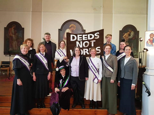 A group of people, wearing sashes that read 'Votes for Women', gathered in a chapel. A large banner reading 'Deeds not Words' is held up at the back.