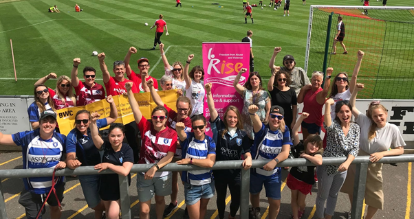 Group of male and female footballers, plus family members and supporters, at the edge of a football pitch. Everyone has their right arm raised, right hand held in a fist. In the background is a banner for Rise, a Brighton-based charity working with people affected by domestic abuse.