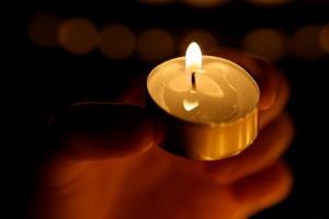 A lit tea light, shining a light on male violence against women.
