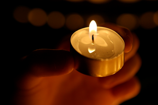 A lit tealight - shining light on male violence against women.