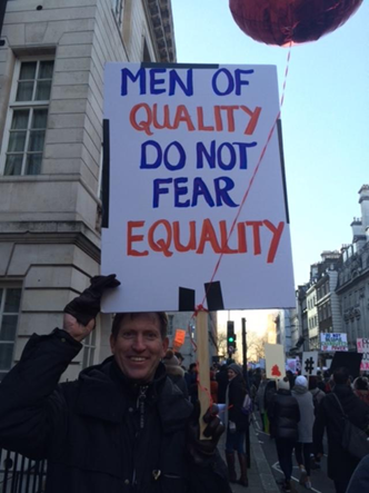 Man holding up a placard that reads 'Men of quality do not fear equality'.
