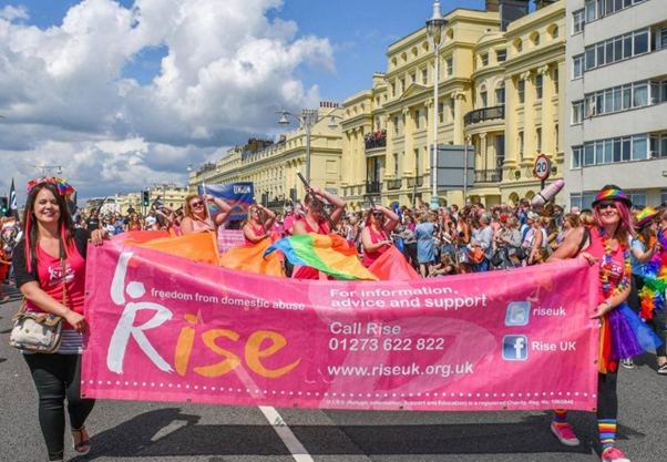 """Colourfully dressed people at Brighton Pride. Two are carrying a banner that reads: """"Rise - freedom from domestic abuse. For information, advice and support call Rise 01273 622822, www.riseuk.org.uk"""""""