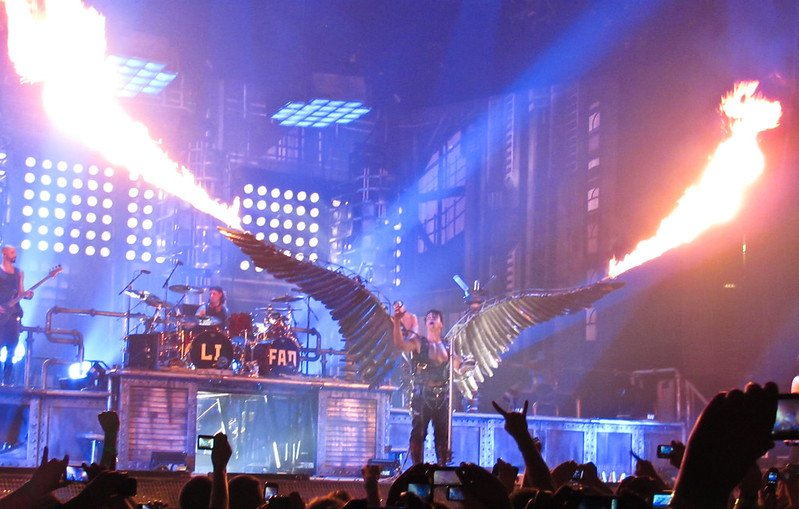 Live photo of the band Rammstein at a concert in New York showing the lead singer wearing angel's wings blowing fire.