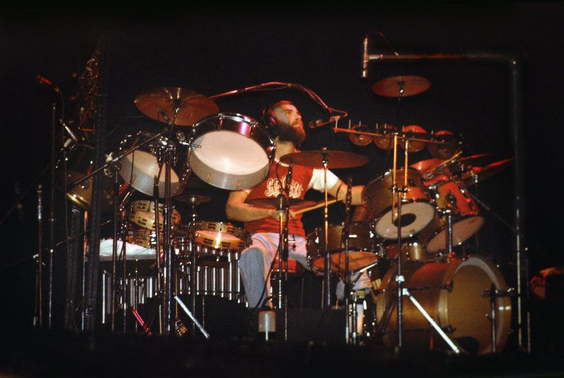 Phil Collins sitting behind his drum kit playing for Genesis in the 1970s.