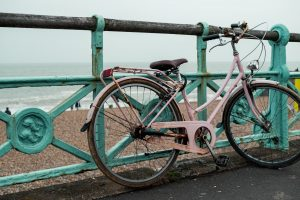Bicycle chained on seafront railing.