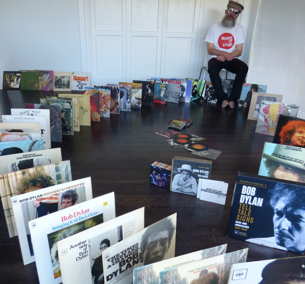 The author, seated, with his full set of Bob Dylan albums stretching round a room