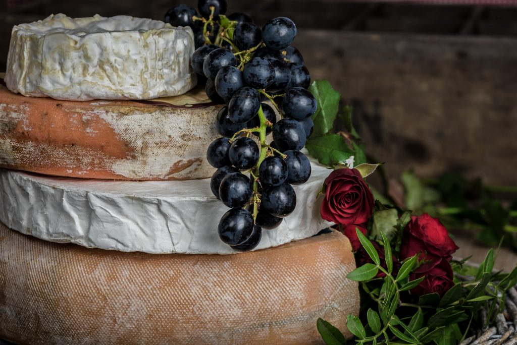 French cheeses and grapes with roses - photo by Jez Timms on Unsplash