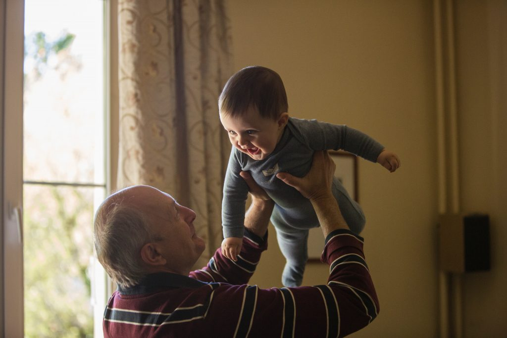 A doting grandfather lifts up his infant childchild who is smiling back