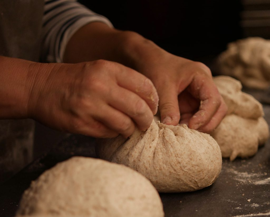Hands shaping doughy loaves during the early stages of baking